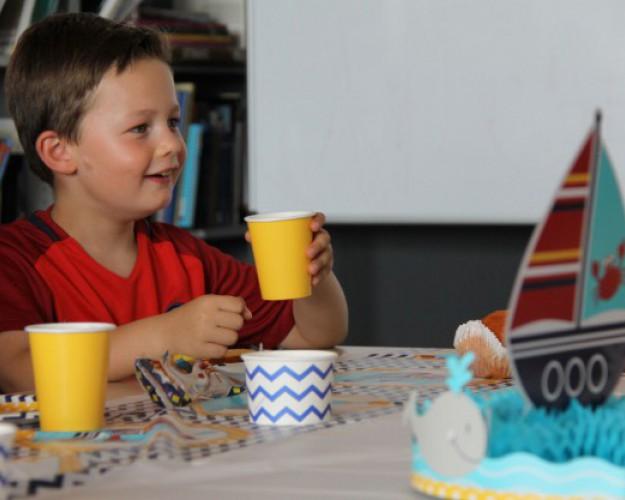 enfant avec gobelet fêtant son anniversaire